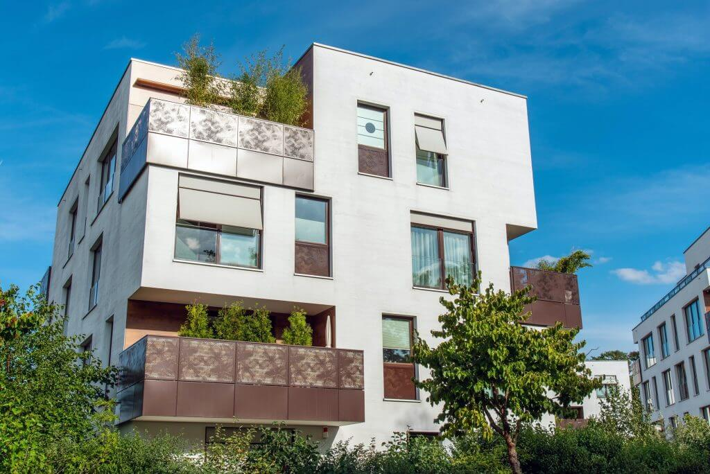 Modern white apartment house with metal balconies