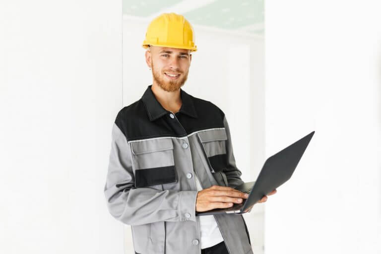 Young smiling engineer in work clothes and yellow hardhat joyful
